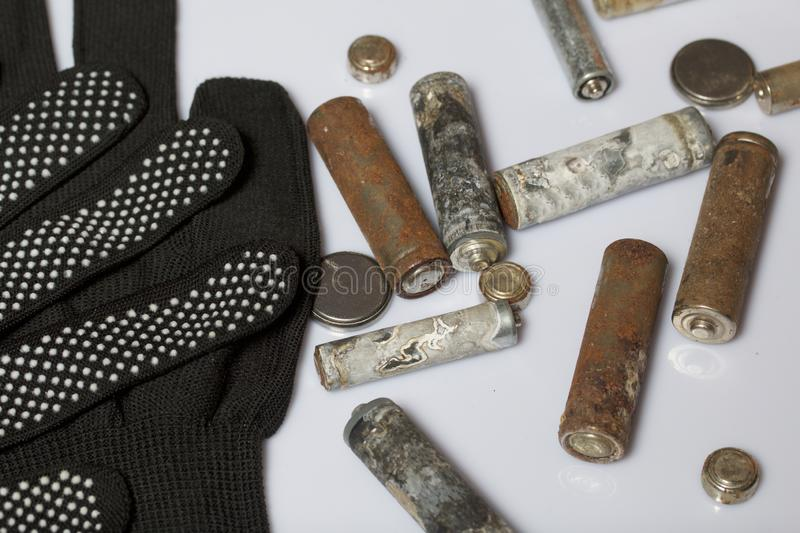 Used finger-wound batteries covered with corrosion. They lie on a wooden box. Next working gloves. Recycling. stock photo