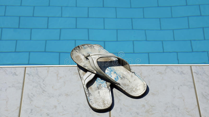 Used flip flops at a pool. Used men white flip flops at a pool royalty free stock image