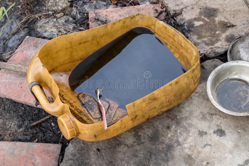 Black Dirty Used Diesel Oil in Recycled Plastic Bottle with Reused Toothbrush - Cleaning and Repairing stock photo