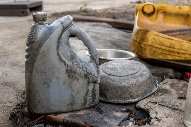 Used Gray Diesel Oil Bottle with no Label - Dirty Greasy Aluminum Bowl on Old Concrete Ground royalty free stock photo