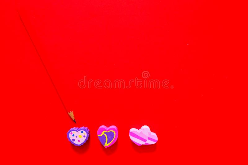 Used Love Pink and Purple Eraser Symbol for Valentine Day Concept. Education Toy Top View. Colorful Heart Erasers and Red Pencil stock photos