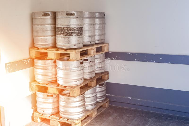Used metal beer keg barrel on wooden pallets in corner of warehouse after delivery. Steel drink containers storage stock photos