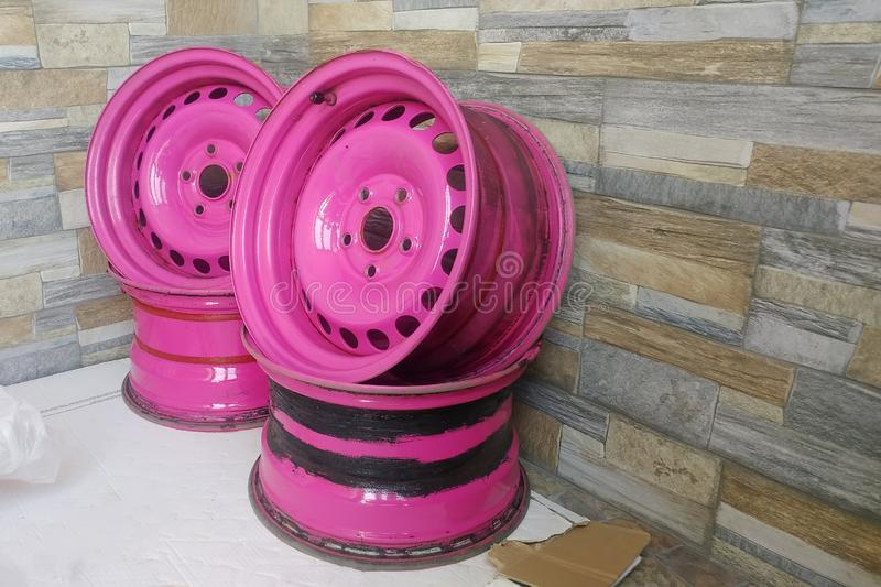 Used Metal stamped rims for cars. Custom made pink steel wheels on the stone wall background royalty free stock image