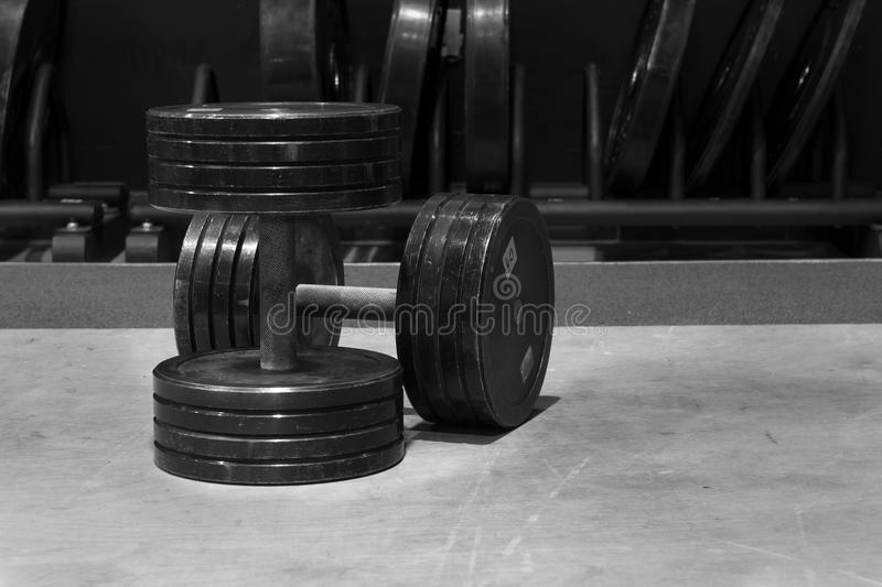 Used and old black gym dumbbells, black and white image, photo. royalty free stock photos