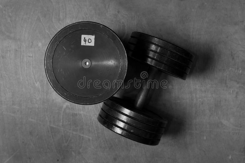 Used and old black gym dumbbells, black and white image, photo. royalty free stock image