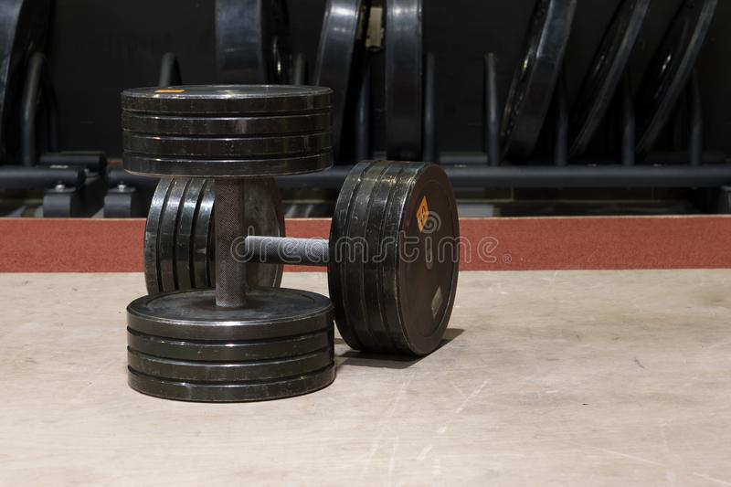Two old and used gym black metal dumbbells. royalty free stock photo