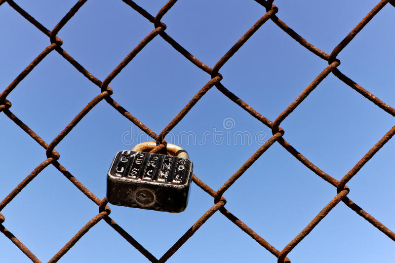 Used Padlock as token for Love. Urban love can be seen at this rusty wire-mesh where the relationship is engraved on the padlock royalty free stock images