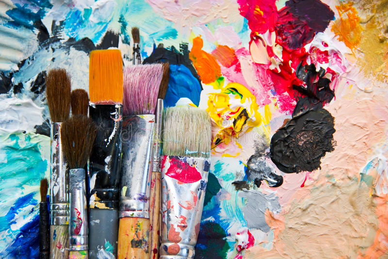 Used paint brushes on a colorful palette stock image
