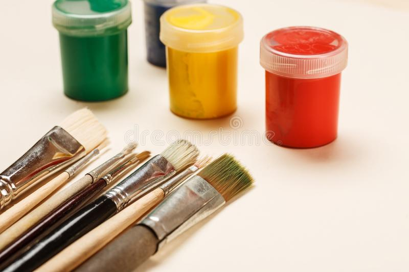 Used paint brushes and paint jars on a table royalty free stock photography