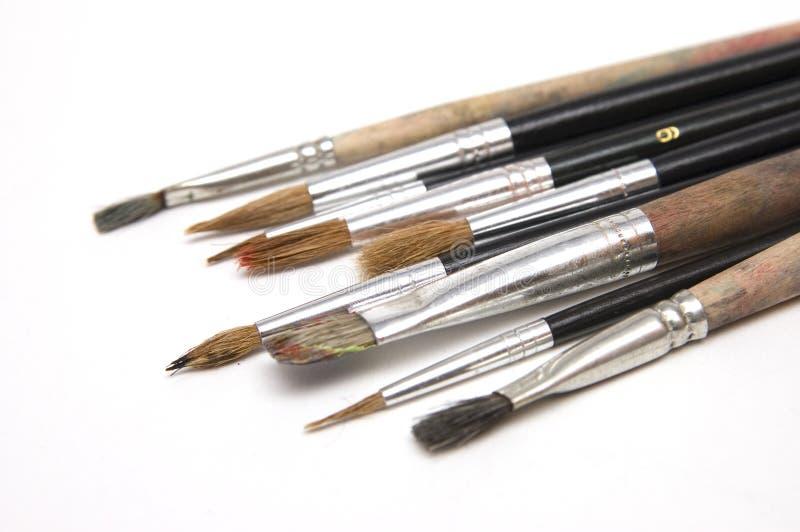 Used paint brushes on white stock image