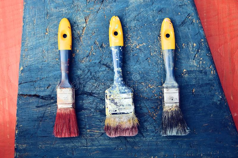 Used paint brushes on wooden background royalty free stock images