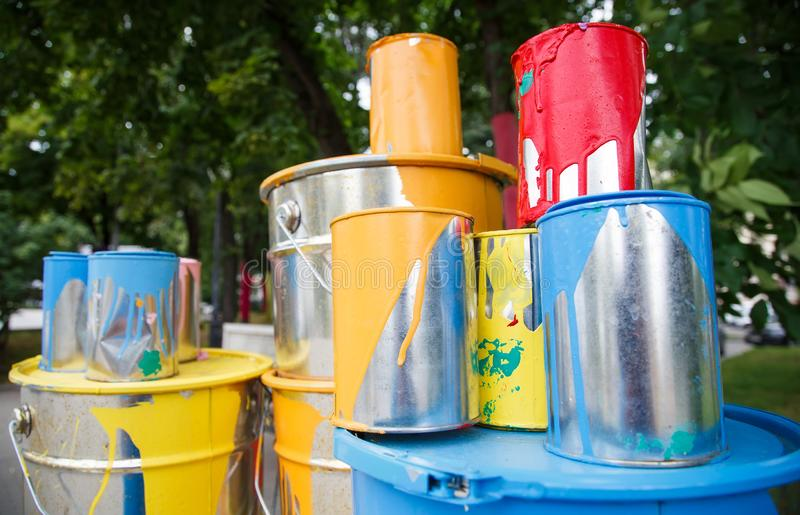 The used paint cans. Many multi-colored buckets with traces of paint on them.  royalty free stock images