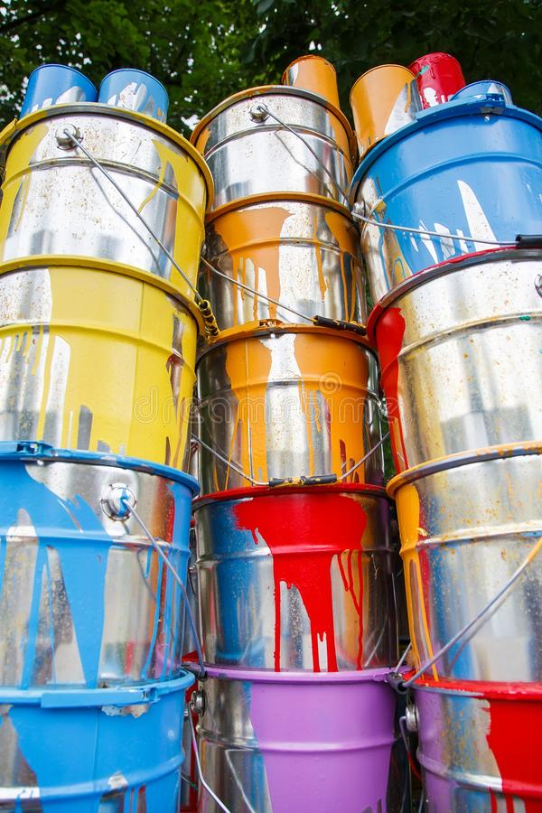 The used paint cans. Many multi-colored buckets with traces of paint on them.  stock photo