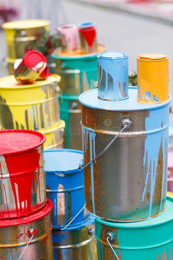 The used paint cans. Many multi-colored buckets with traces of paint on them.  stock images