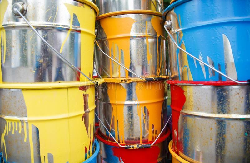 The used paint cans. Many multi-colored buckets with traces of paint on them.  stock photography