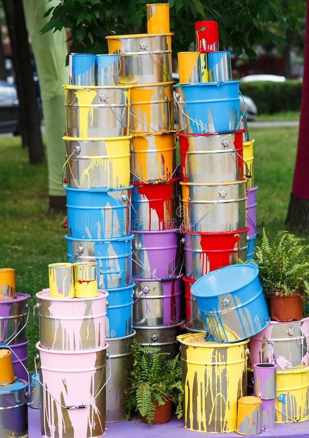 The used paint cans. Many multi-colored buckets with traces of paint on them.  royalty free stock photo
