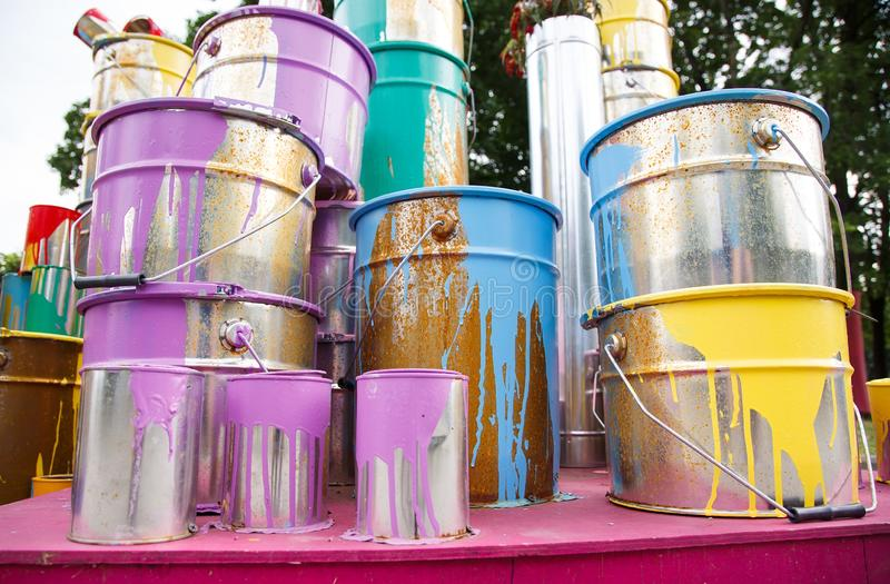 The used paint cans. Many multi-colored buckets with traces of paint on them.  royalty free stock image