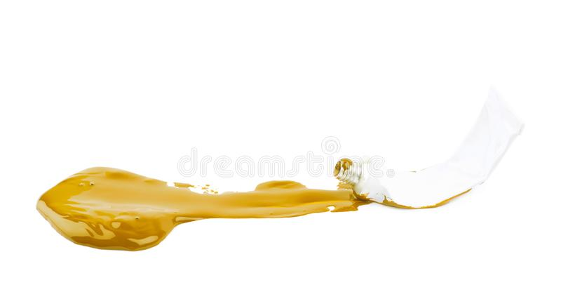 Paint tube in a dye spill isolated. Used paint tube lying in a dye spill splash, composition isolated over the white background stock photography