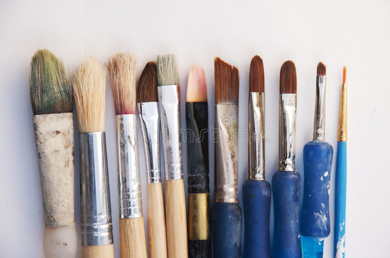Used painting brushes. Old used painting small to large brushes on the white background stock photos