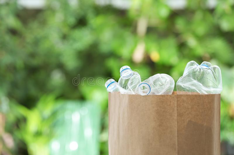 Used plastic bottles in paper bag on blurred background. Recycling problem. Used plastic bottles in paper bag on blurred background, space for text. Recycling stock photo