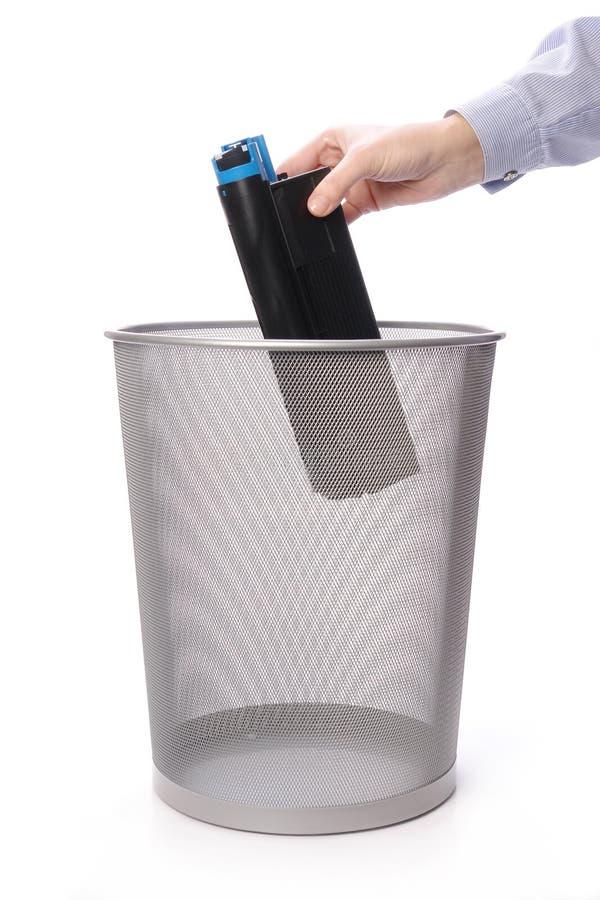 Used printer cartridge. Female hand throwing used laser printer cartridge into metal trash bin over white royalty free stock photography