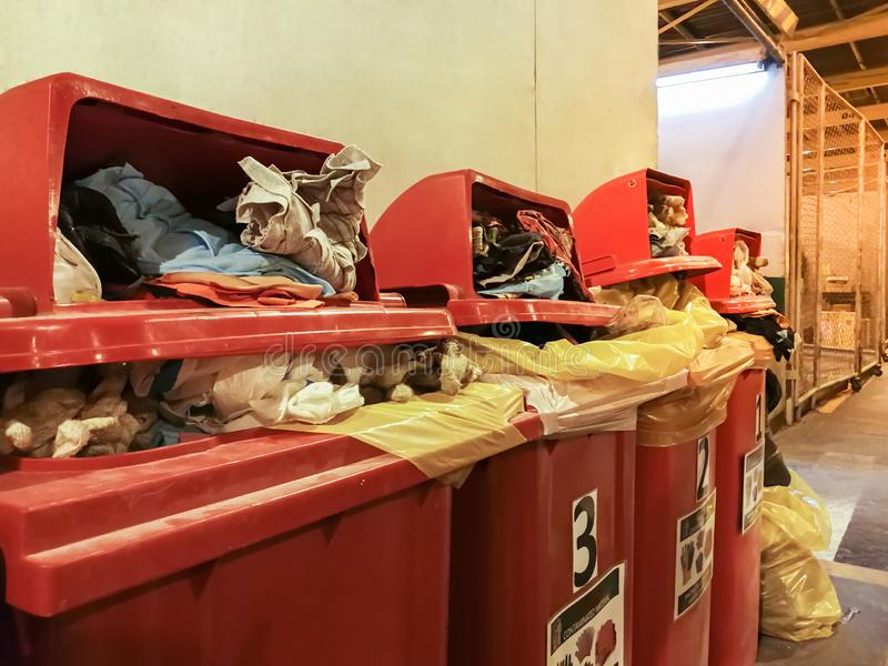 Used rag and glove cotton contaminated with oil sorted in red garbage bin in the factory,Full red trash containers royalty free stock photography