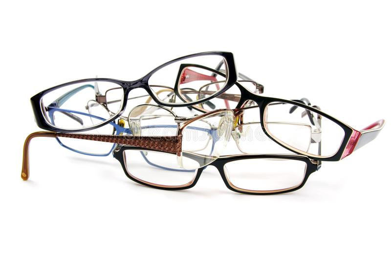 Stack of old reading glasses. Used reading glasses stacked in a pile on a white background stock images