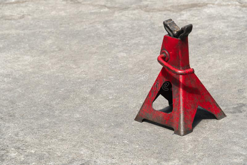 Used red high lift jack stand. On the floor stock photos