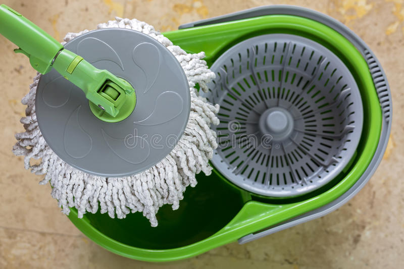 Used round spin mop with microfiber head, green handle on cleaning bucket royalty free stock image