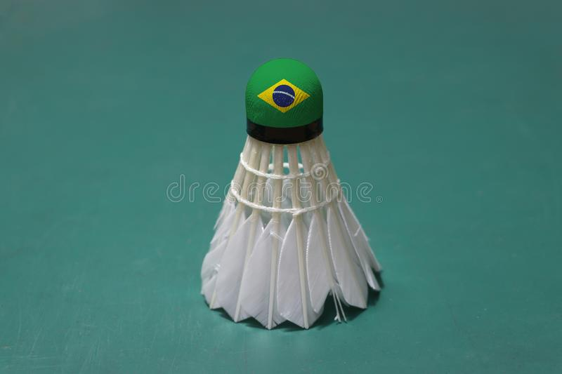 Used shuttlecock and on head painted with Brazil flag put vertical on green floor of Badminton court. Badminton sport concept royalty free stock images