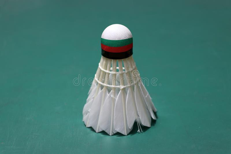 Used shuttlecock and on head painted with Bulgaria flag put vertical on green floor of Badminton court. Badminton sport concept stock photography