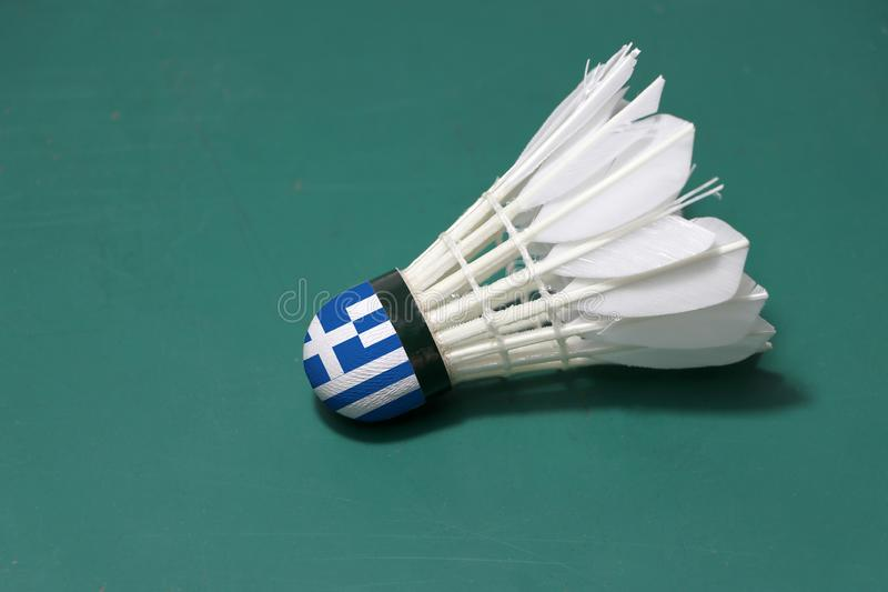 Used shuttlecock and on head painted with Greece flag put horizontal on green floor of Badminton court. Badminton sport concept stock photos
