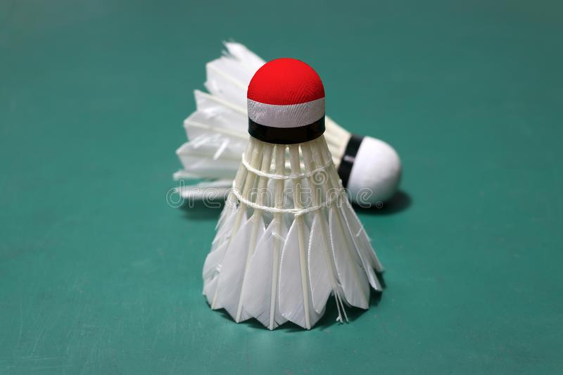 Used shuttlecock and on head painted with Indonesia flag put vertical and out focus shuttlecock put horizontal on green floor of. Badminton court. Badminton royalty free stock photography