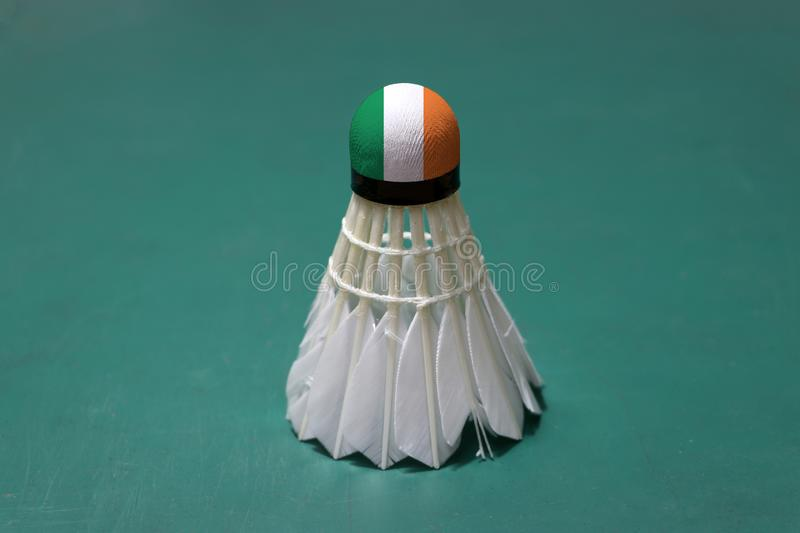 Used shuttlecock and on head painted with Ireland flag put vertical on green floor of Badminton court. Badminton sport concept royalty free stock images