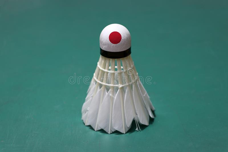 Used shuttlecock and on head painted with Japan flag put vertical on green floor of Badminton court. Badminton sport concept royalty free stock photo
