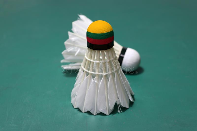 Used shuttlecock and on head painted with Lithuania flag put vertical and out focus shuttlecock put horizontal on green floor of. Badminton court. Badminton stock photography