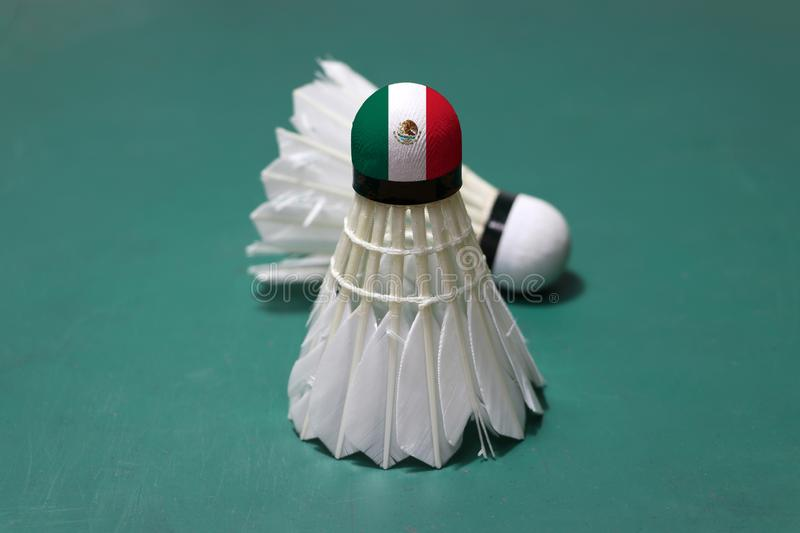 Used shuttlecock and on head painted with Mexico flag put vertical and out focus shuttlecock put horizontal on green floor of. Badminton court. Badminton sport royalty free stock photos