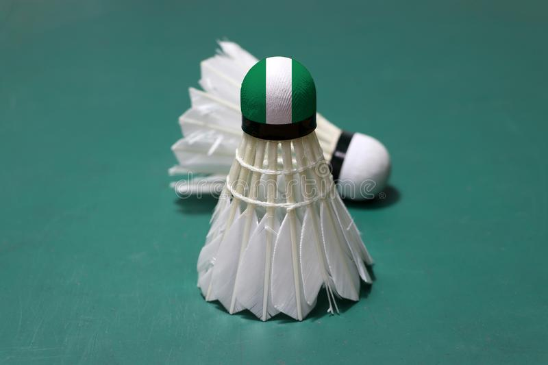 Used shuttlecock and on head painted with Nigeria flag put vertical and out focus shuttlecock put horizontal on green floor of. Badminton court. Badminton sport royalty free stock photography