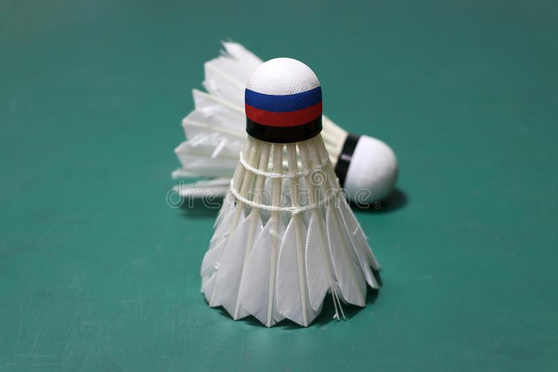 Used shuttlecock and on head painted with Russia flag put vertical and out focus shuttlecock put horizontal on green floor of. Badminton court. Badminton sport royalty free stock image