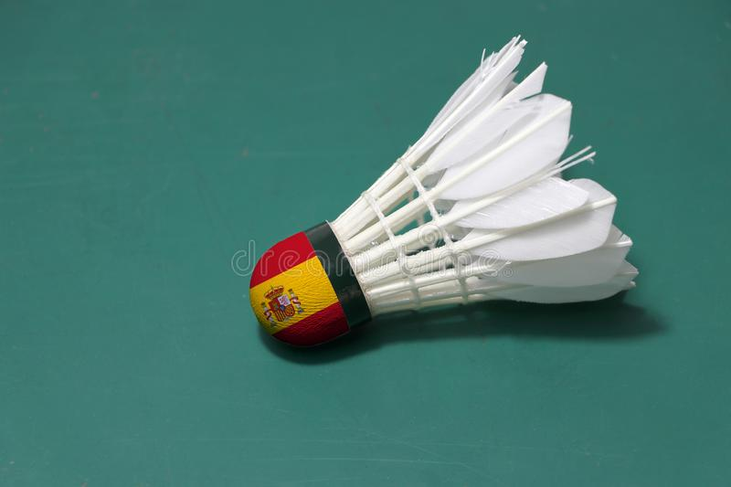 Used shuttlecock and on head painted with Spain flag put horizontal on green floor of Badminton court. Badminton sport concept stock image