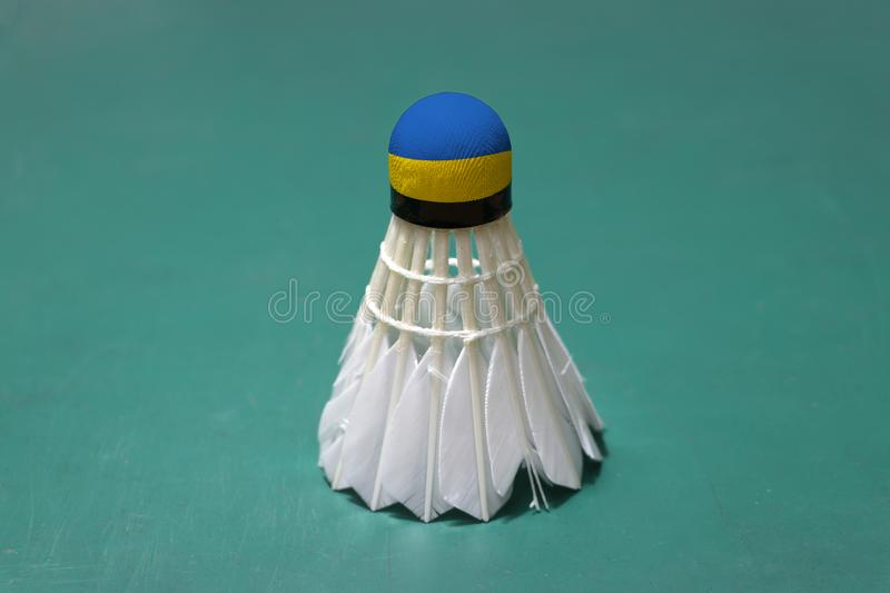Used shuttlecock and on head painted with Ukraine flag put vertical on green floor of Badminton court. Badminton sport concept royalty free stock image