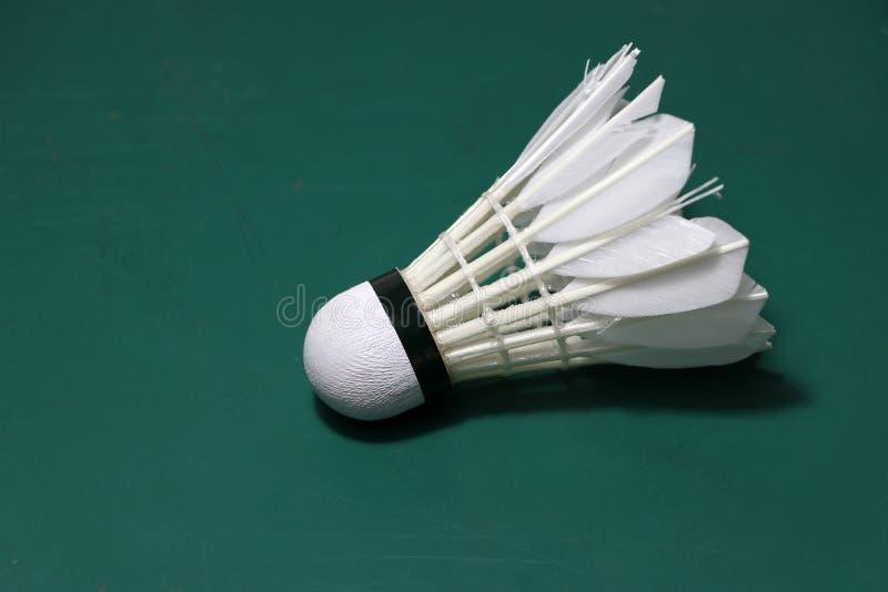 Used shuttlecock put horizontal on green floor of Badminton court. Badminton sport concept stock photography