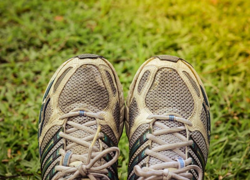 Used sport shoes on yard background stock image