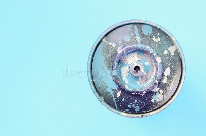 Used spray can with blue paint drips lie on texture background of fashion pastel blue color paper royalty free stock images