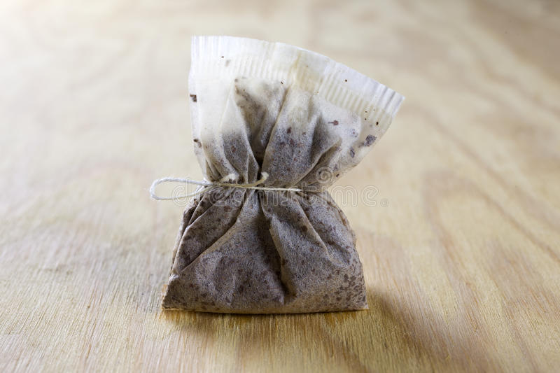 Used tea bag. On a wooden table royalty free stock image
