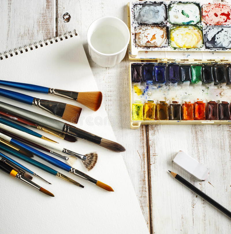 Used water-color paint-box, watercolor paper and paint brush. Top view royalty free stock photography