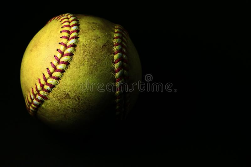A used yellow softball isolated on a black background. A used yellow softball with red seams isolated on a black background stock images
