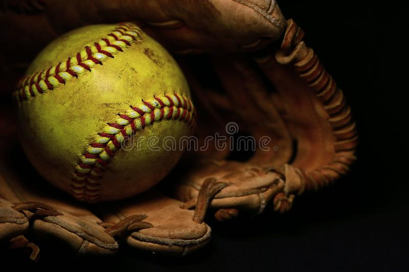 A yellow softball in an old, brown, leather glove. A used yellow softball with red seams in an old, brown, leather glove stock photos