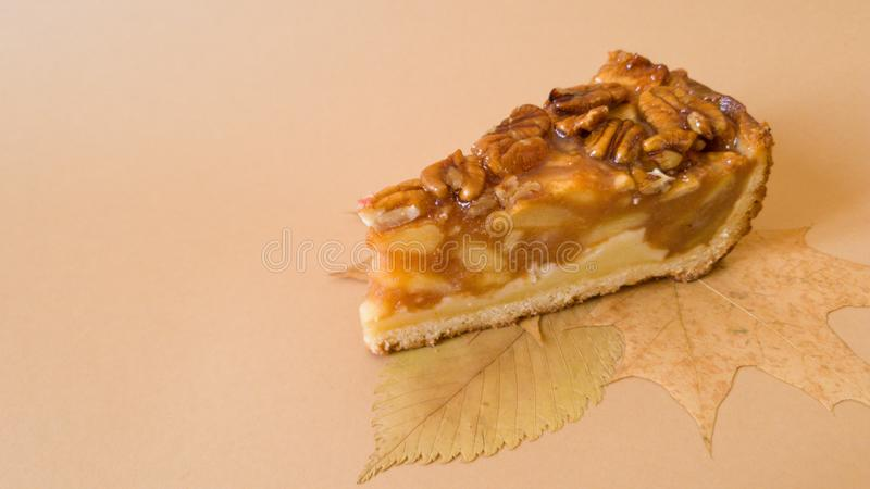 Useful baking.  An appetizing piece of apple pie with pecans on autumn leaves on a plain light brown background. Useful baking.  An apple, fruit, dessert, pie stock photos