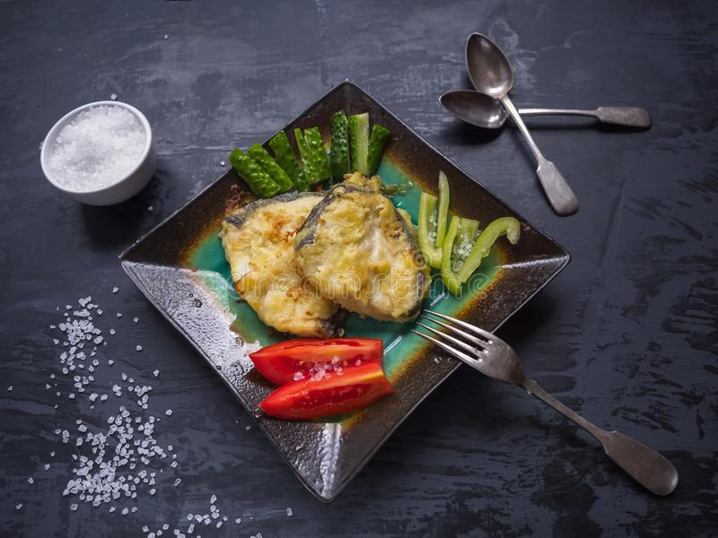 A useful breakfast of fried cod and fresh vegetables royalty free stock image